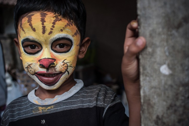 A boy with a painted tiger face poses before the Grebeg Ritual in Tegallalang, Bali, Indonesia. During the biannual ritual young members of the community parade through the village with painted faces and bodies to ward off evil spirits. (Putu Sayoga/Getty Images)