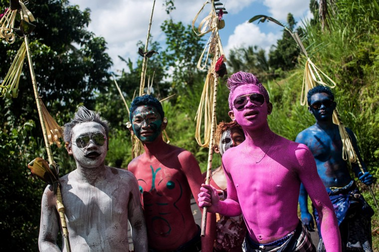 Young members of the village community walk around their village with painted bodies during the Grebeg Ritual in Tegallalang, Bali, Indonesia. During the biannual ritual young members of the community parade through the village with painted faces and bodies to ward off evil spirits. (Putu Sayoga/Getty Images)