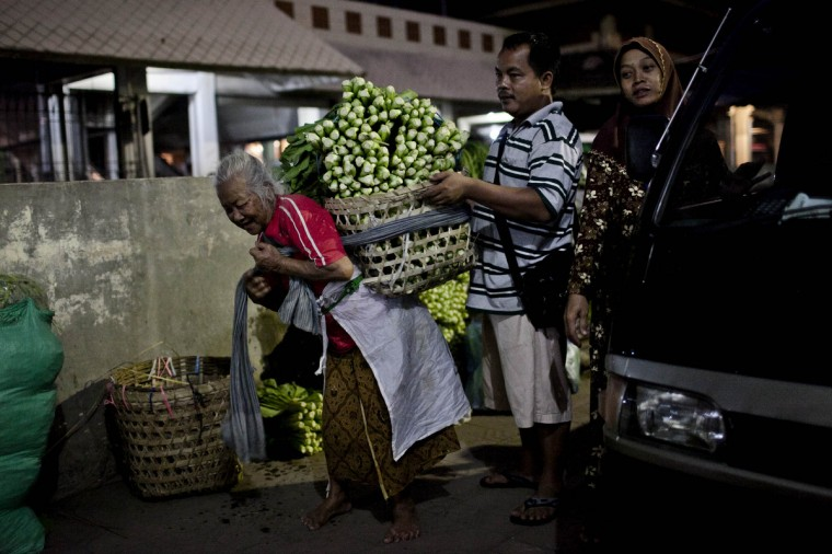 Waginah (85), a female porter, has her basket of vegetables loaded onto her back at Beringharjo traditional market in Yogyakarta, Indonesia. These female porters earn their living carrying fruit, vegetables and dry goods among other items, in baskets strapped to their backs starting work in the early hours and finishing late in the day. It is reported that on a busy day at the market, the average porter will earn an income of Rp 35.000 or US$37 per day. Labor day is celebrated across South East Asia on May 1st and is seen as an opportunity to acknowledge the social and economic accomplishments of the workers. (Ulet Ifansasti/Getty Images)
