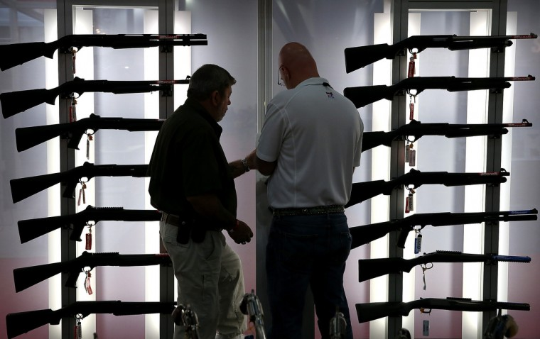 Attendees look at a display of tactical shotguns during the 2013 NRA Annual Meeting and Exhibits at the George R. Brown Convention Center on May 3, 2013 in Houston, Texas. (Justin Sullivan/Getty Images)