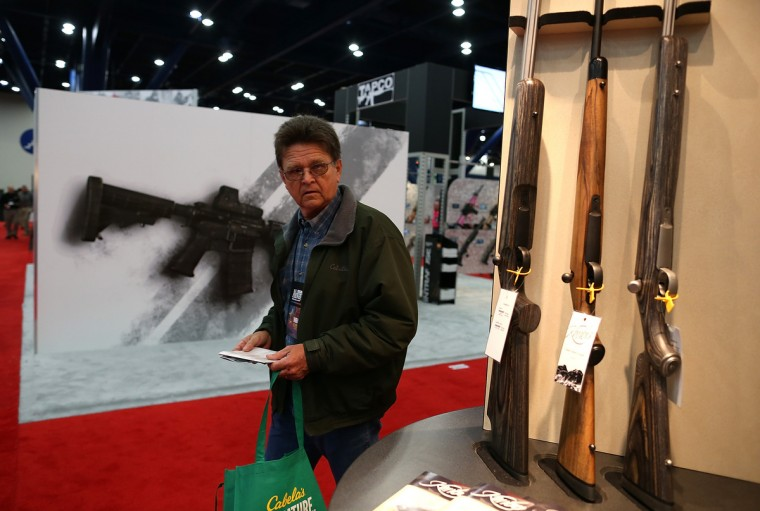 An attendee looks at a display of shotguns during the 2013 NRA Annual Meeting and Exhibits at the George R. Brown Convention Center. (Justin Sullivan/Getty Images)