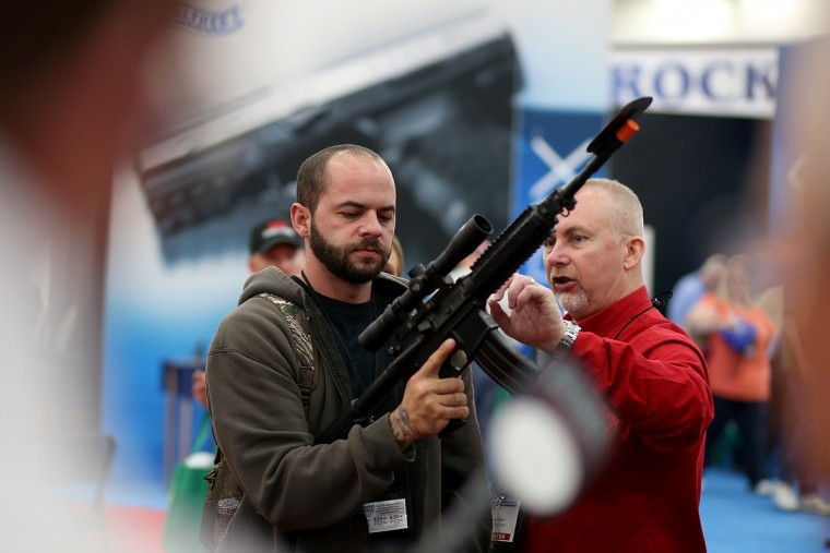 An attendee inspects a scope on an assault rifle during the 2013 NRA Annual Meeting and Exhibits at the George R. Brown Convention Center on May 3, 2013 in Houston, Texas. (Justin Sullivan/Getty Images)