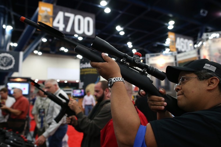 An attendee inspects a scope during the 2013 NRA Annual Meeting and Exhibits at the George R. Brown Convention Center on May 3, 2013 in Houston, Texas. (Justin Sullivan/Getty Images)