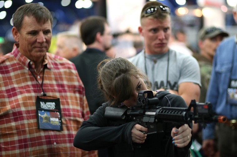 An attendee uses a gun to play a shooting game during the 2013 NRA Annual Meeting and Exhibits at the George R. Brown Convention Center on May 3, 2013 in Houston, Texas. (Justin Sullivan/Getty Images)
