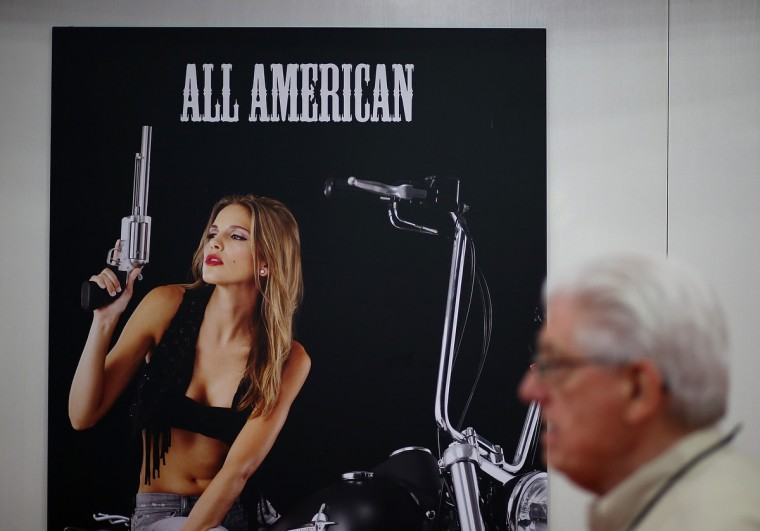 An attendee walks by a poster during the 2013 NRA Annual Meeting and Exhibits at the George R. Brown Convention Center on May 3, 2013 in Houston, Texas. (Justin Sullivan/Getty Images)