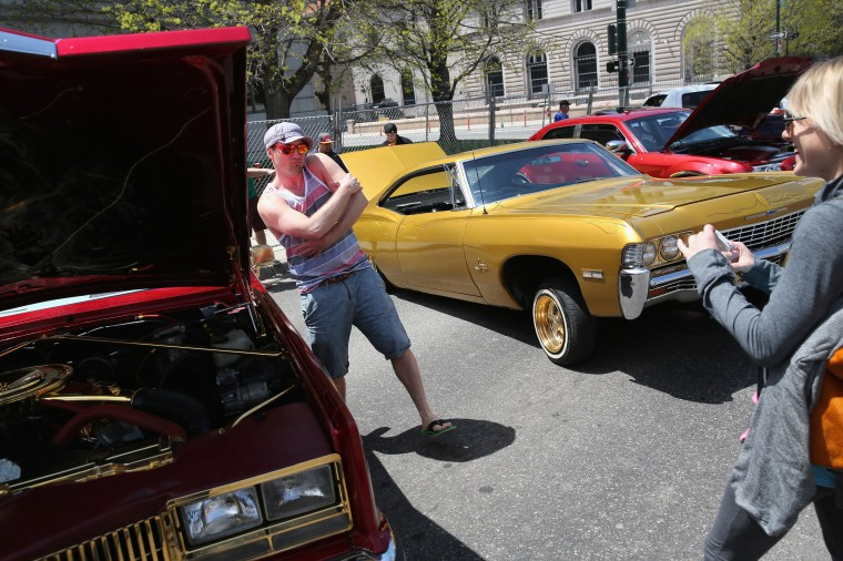 People take photos in front of low riders at the Cinco de Mayo celebration in Denver, Colorado. (John Moore/Getty Images)