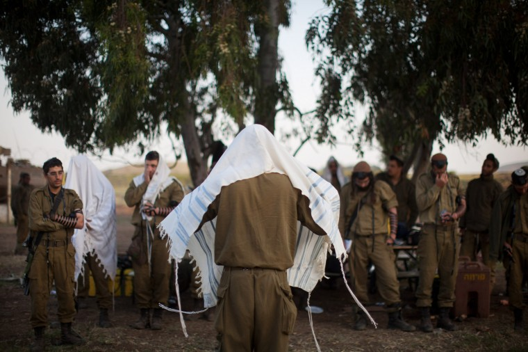 Israeli soldiers of the Golani brigade pray while taking part in a military exercise near the border with Syria, in the Israeli-annexed Golan Heights. Syria has accused Israel of launching a series of airstrikes on targets near the Lebanon/Syria border, including an arms shipment and the Jamraya research centre, that was thought to produce chemical weapons. (Uriel Sinai/Getty Images)