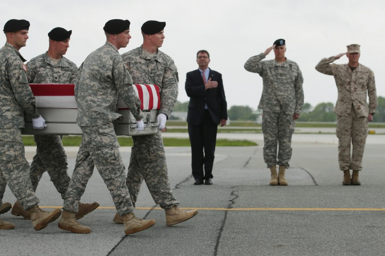 A U.S. Army carry team carries the flag-draped transfer case with the remains of Army 1st Lt. Brandon Landrum across the tarmac at Dover Air Force Base as (L-R) Deputy Secretary of Defense Ashton Carter, Army Maj. Gen. William Rapp and Marine Col. Christian Cabaniss salute in Dover, Delaware. A member of the 1st Brigade Combat Team, 1st Armored Division, Landrum and four other soliders were killed May 4 when their vehicle hit a roadside bomb during a patrol in the Maiwand District in Kandahar Province, Afghanistan. (Chip Somodevilla/Getty Images
