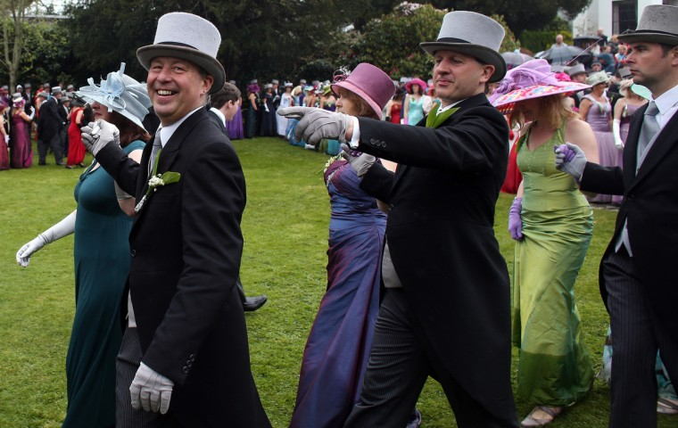 People dance in the grounds of Lismore House and Gardens in the centre of Helston, as they take part in the midday dance to celebrate Helston Flora Day in Cornwall, England. The annual Flora Dance, also known as the Furry Dance, is one of the UK's oldest customs still practiced today and is said to be a celebration of the passing of Winter and the arrival of Spring. A series of dances take place throughout the day, beginning at 7am, all over the Cornish town and even in and out of private houses and shops. However the highlight is the midday dance which was traditionally the dance of the gentry in the town and is why men still wear top hats and tails while the women dance in their finest dresses. (Matt Cardy/Getty Images)