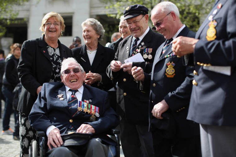 John Clarke (2nd L), a Veteran of the Battle of the Atlantic who served in the Merchant Navy, speaks with friends outside St. Paul's cathedral before a service to mark the 70th anniversary of the battle of the Atlantic in London, England. The 'Battle of the Atlantic' was the longest continuous military campaign of World War II; thousands of merchant ships were sunk and tens of thousands of lives were lost. (Oli Scarff/Getty Images)