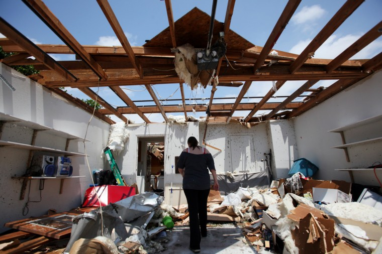 Beth Poledna, 28, walks through what's left of her garage as she begins the clean up process after a tornado destroyed parts of her home May 16, 2013 in Cleburne, Texas. Poledna's family took shelter in their bathroom as the tornado destroyed areas of their home. (Ben Torres/Getty Images)