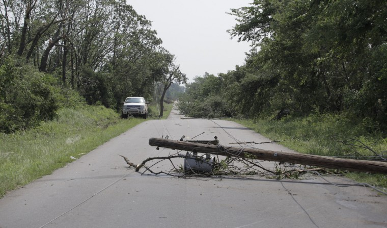 An electrical pole lies on a Pottawatomie County road after a tornado May 20, 2013 near Shawnee, Oklahoma. A series of tornados moved across central Oklahoma May 19, killing two people and injuring at least 21. (Brett Deering/Getty Images)