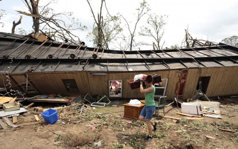 A volunteer helps clean up Jean McAdams' mobile home after it was overturned by a tornado May 20, 2013 near Shawnee, Oklahoma. A series of tornados moved across central Oklahoma May 19, killing two people and injuring at least 21. (Brett Deering/Getty Images)