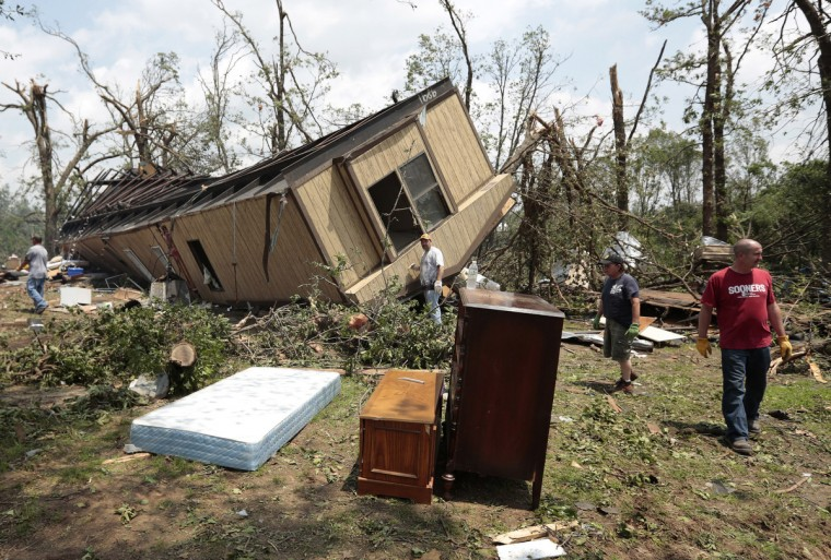 Volunteers help clean out Jean McAdams' mobile home after it was overturned by a tornado May 20, 2013 near Shawnee, Oklahoma. A series of tornados moved across central Oklahoma May 19, killing two people and injuring at least 21. (Brett Deering/Getty Images)