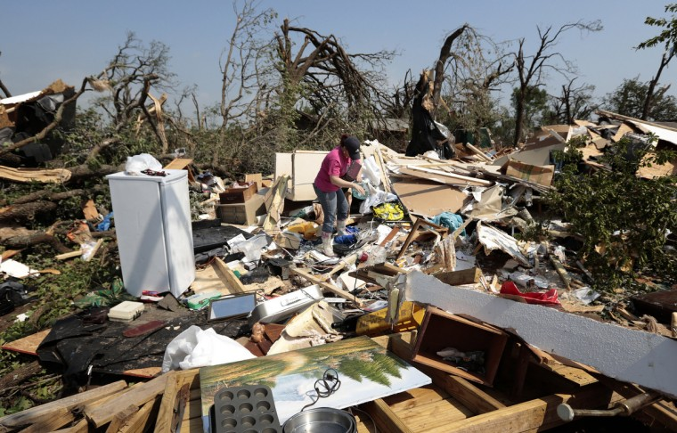 Kasey Clark sorts through the debris of her grandmother-in-law Thelma Cox's mobile home after it was destroyed by a tornado May 20, 2013 near Shawnee, Oklahoma. A series of tornados moved across central Oklahoma May 19, killing two people and injuring at least 21. (Brett Deering/Getty Images)