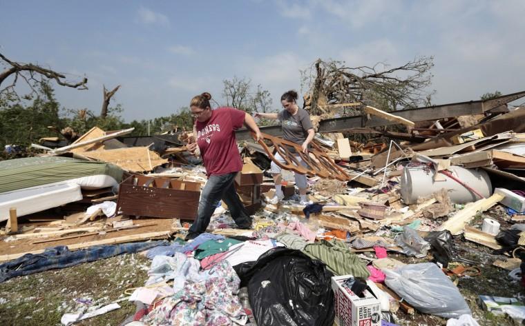 Candice Lopez (L) and Stephanie Davis help clean debris from Thelma Cox's mobile home after it was destroyed by a tornado May 20, 2013 near Shawnee, Oklahoma. A series of tornados moved across central Oklahoma May 19, killing two people and injuring at least 21. (Brett Deering/Getty Images)