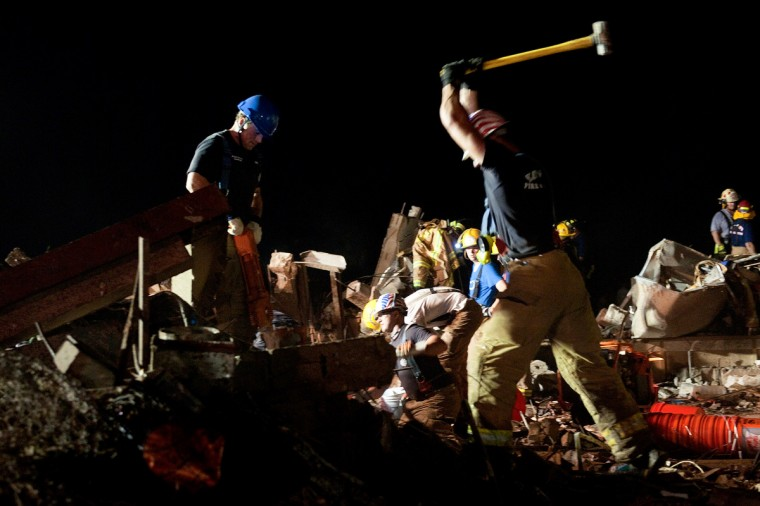 In this handout provided by the U.S. Department of Defense, two firefighters break through concrete during the search for survivors in the remains of the Plaza Towers Elementary School after it was hit by a tornado on May 20, 2013 in Moore, Oklahoma. The town reported a tornado to be at least EF4 strength and two miles wide that touched down Monday killing at least 24 people and leveling everything in its path. U.S. President Barack Obama promised federal aid to supplement state and local recovery efforts. (Maj. Geoff Legler/Oklahoma National Guard)