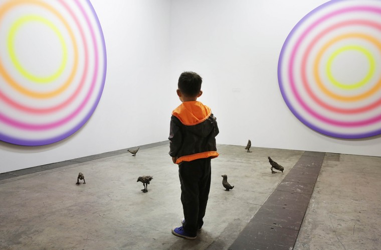 A little boy looks at art works on the floor and wall by Ugo Rondinone, which are represented by gallery Galerie Eva Presenhuber at Art Basel, May 22, 2013 in Hong Kong. (Jessica Hromas/Getty Images)