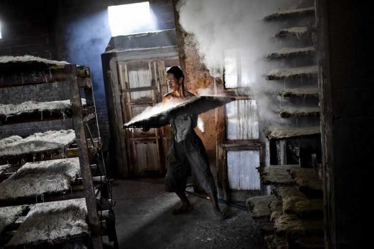 A worker carries noodles or mie lethek after the steaming process at mie lethek factory in Srandakan village, Bantul in Yogyakarta, Indonesia. Yasir Feri Ismatrada took on the family business of mie lethek production founded by his late grandfather. A one-ton stone cylinder is rotated by cows in order to grind the flour, a technique rarely seen today. Yasir puts great importance on the fair treatment of his 40 employees with management profits capped at 10%, prioritizing the interests of the staff. Mie lethek are sold for Rp 8,000 or US$80 cents per kilogram. (Ulet Ifansasti/Getty Images)