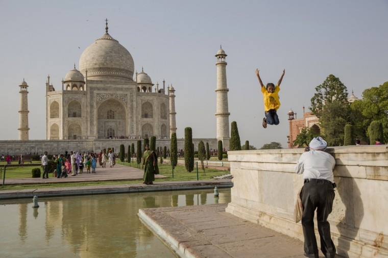 An Indian girl poses for a photograph as tourists visit the Taj Mahal in Agra, India. Completed in 1643, the mausoleum was built by the Mughal emperor Shah Jahan in memory of his third wife, Mumtaz Mahal, who is buried there alongside Jahan. (Daniel Berehulak/Getty Images)