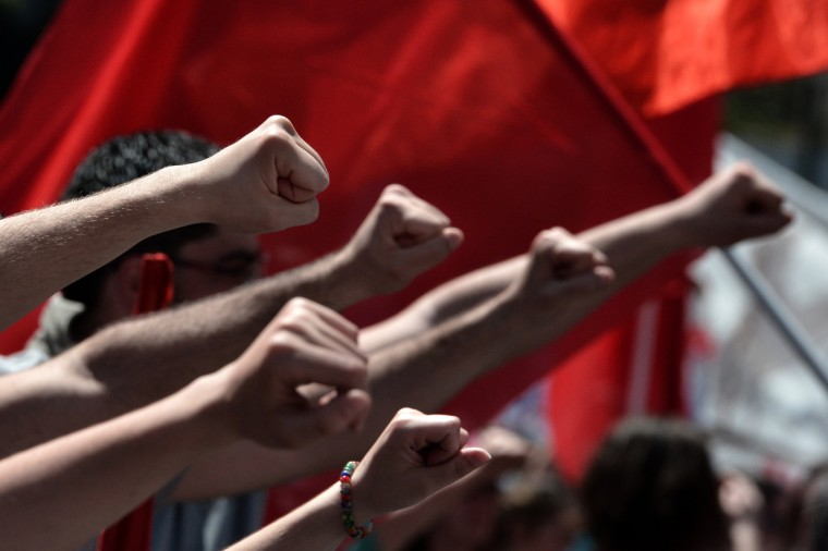 Demonstrators raise their fists during a demonstration. A strike stopped ferry services to the Greek islands and disrupted public transport in the capital Athens ahead of May Day protests Wednesday against Greece's prolonged economic austerity policies. (Aris Messinis/Getty Images)