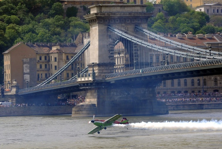 Hungarian aerobatics pilot and European champion air racer Zoltan Veres flies with his aircraft under the oldest Hungarian bridge, the 'Chain Bridge' and over the Danube River in Budapest during an air show. (Attila Kisbenedek/Getty Images)