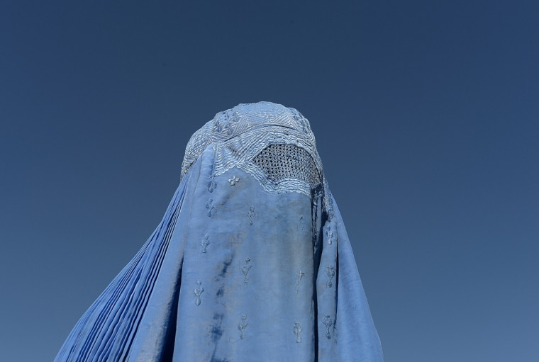 """A burqa-clad Afghan protester takes part in a demonstration staged by a pro-democracy faction in Kabul. Some hundred supporters of a pro-democracy faction took to the streets to """"condemn"""" the victory day of the former pro-communist regime of 1970s followed by the victory of former anti-Soviet Mujahedin that also marked the start of Afghanistan's civil war between 1992 and 1996. (Shah Marai/Getty Images)"""