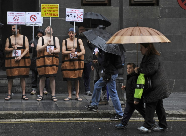 People walk past three men in barrel costumes holding placards against government's social cuts during a protest called by several social groups in front of the ruling Basque Nationalist Party (PNV) headquarters in the northern Spanish city of Bilbao. AFP PHOTO/ (Rafa Rivas/Getty Images)