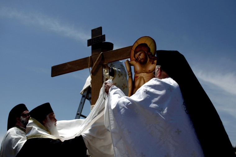 Greek Orthodox priests carry out the Apokathelosis, the removal of Christ's dead body from the Cross, which forms a key part of Orthodox Easter, in a ceremony at the Church of the Dormition of the Virgin in Penteliin Penteli, north Athens. (Angelos Tzortzinis/Getty Images)