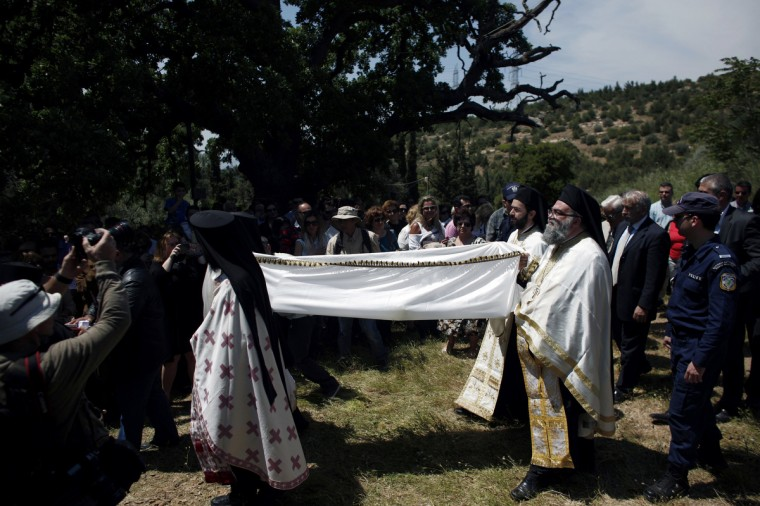 """Greek Orthodox priests carry out the Apokathelosis, carrying the """"body"""" of Jesus Christ to a tomb, which forms a key part of Orthodox Easter, in a ceremony at the Church of the Dormition of the Virgin in Penteliin Penteli. (Angelos Tzortzinis/Getty Images)"""