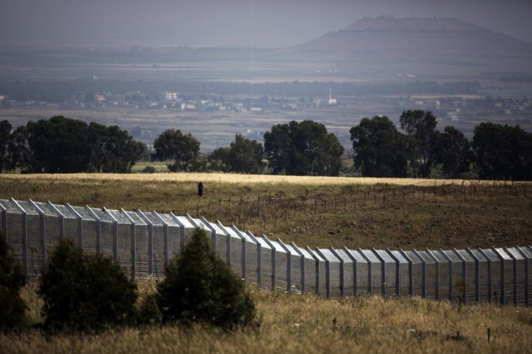 A picture taken from the Israeli side of the border shows a Syrian woman waking near the Syria-Israel boundary fence in the Israeli annexed Golan Heights near the southern Syrian village of Ar Rafide as fighting continues to ravage Syria. The number of Syrians displaced within their homeland by the vicious civil war has reached 4.25 million, the UN humanitarian office. (Menahem Kahana/AFP/Getty Images