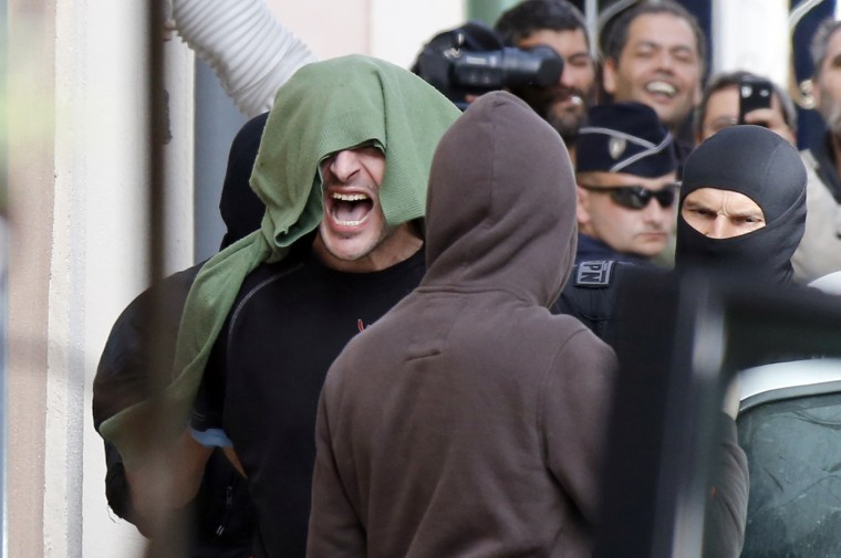 """An ETA suspected member (Left) shouts as he is arrested at his home in the Figuerolles neighbourhood of Montpellier, southern France, as five other suspect were arrested today by French police in Blois, a city in central France, Brive-la-Gaillarde and Montpellier. This arrests of six ETA suspects in France broke up the Basque armed separatist group's """"logistical core"""" and have made its total dissolution inevitable, Spain's interior minister said. (Sylvain Thomas/AFP/Getty Images)"""