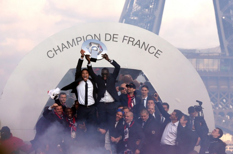 Paris Saint-Germain's players celebrate with their trophy as they parade on a double decker in Paris, one day after Paris secured French L1 football championship title. (Thomas Samson/Getty Images)