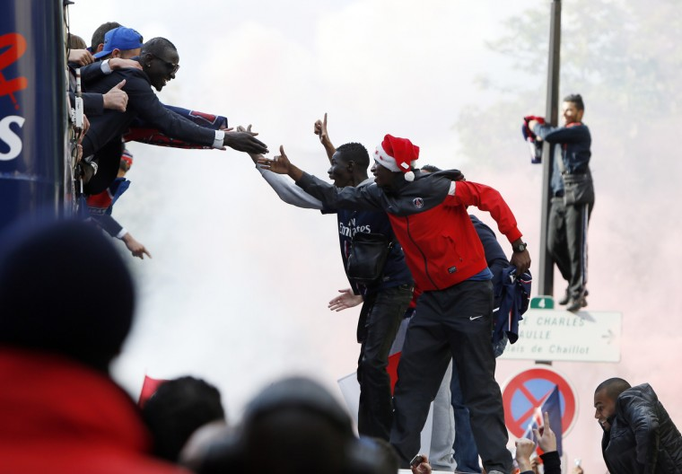 Paris Saint-Germain's players celebrate with supporters as they parade on a double decker bus on May 13, 2013 in Paris, one day after Paris secured French L1 football championship title. (Kenzo Tribouillard/Getty Images)