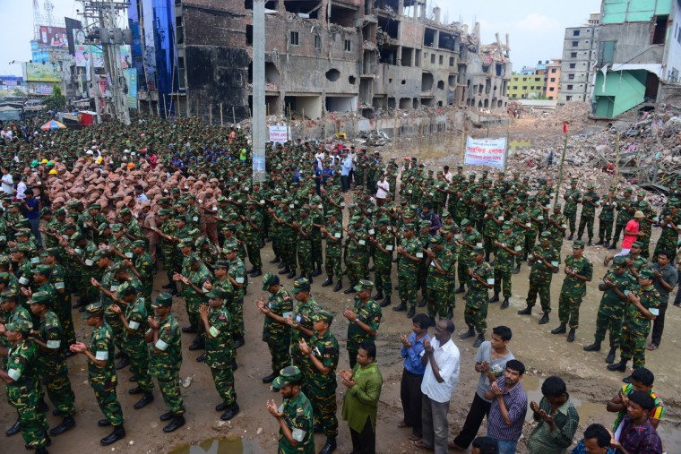 Bangladesh army personnel offer prayer in front of the rubble of a nine-story building collapse in Savar, on the outskirts of Dhaka. Bangladesh's army wrapped up its search May 14, 2013 for bodies in a collapsed nine-storey building outside the capital as dozens of people were still massed at the site for news of their missing relatives. (Munir uz Zaman/Getty Images)