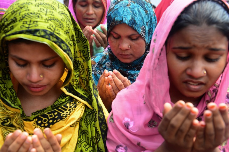 A Bangladeshi family member (C) weeps as she offers prayers with others in front of the rubble of a nine-story building collapse in Savar, on the outskirts of Dhaka. Bangladesh's army wrapped up its search May 14, 2013 for bodies in a collapsed nine-storey building outside the capital as dozens of people were still massed at the site for news of their missing relatives. (Munir uz Zaman/Getty Images)