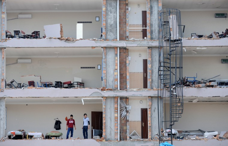 People stand in a damaged building at Reyhanli in Hatay, just a few kilometres from the main border crossing into Syria. The death toll in twin car bombings in a Turkish town near the Syrian border has increased to 50 after another body was recovered and a victim died in hospital, the health minister was quoted as saying on May 14. The attacks also provoked a backlash against Syrian refugees in Turkey, whose number is around 400,000 but government officials have repeatedly warned against provocations and said Turkey will maintain its open-door policy for Syrians fleeing the regime's crackdown. (Bulent Kilic/Getty Images)