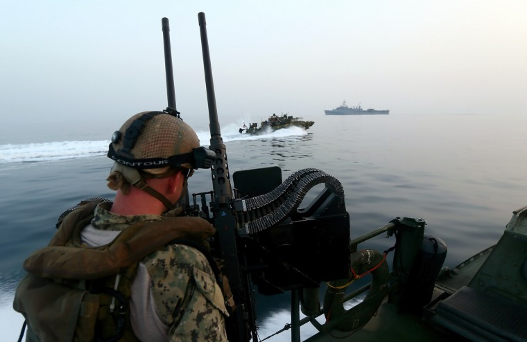 A US navy personnel mans a heavy machine gun as he watches a Riverine Command Boat (C) cruising past the USS Ponci somewhere in the Arabian Sea, on the first day of the the biggest mine countermeasures exercise in the Arabian Gulf. The US Navy along with other 40 nations are conducting the games. (Marwan Naaman/Getty Images)