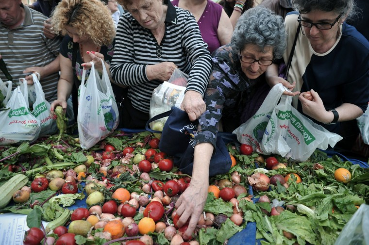 People reach for free fruits and vegetables distributed by farmers' market vendors as part of their protest marking their 24-hour strike on May 15, 2013. Vendors at Greece's open-air street markets are on strike protesting the government's plans to facilitate entry into the profession. (Louisa Gouliamaki/Getty Images)