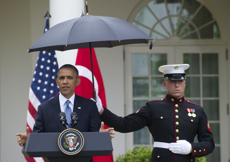 A US Marine holds an umbrella for US President Barack Obama during a brief rain shower as he hold a joint press conference with Turkish Prime Minister Recep Erdogan in the Rose Garden of the White House in Washington, DC. (Saul Loeb/Getty Images)