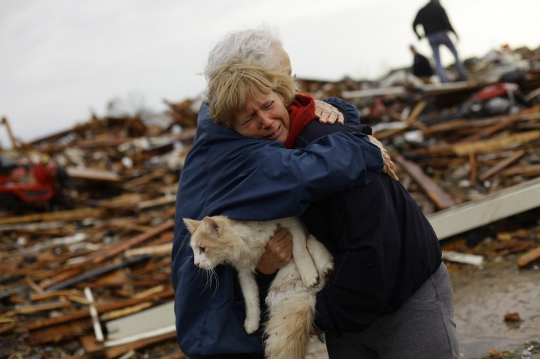 June Simson (R) receives a hug from her neighbor Jo McGee while embracing her cat Sammi after she found him standing on the rubble of her destroyed home on May 21, 2013 in Moore, Oklahoma. Families returned to a blasted moonscape that had been an American suburb Tuesday after a monstrous tornado tore through the outskirts of Oklahoma City, killing at least 24 people. Nine children were among the dead and entire neighborhoods vanished, with often the foundations being the only thing left of what used to be houses and cars tossed like toys and heaped in big piles. (Joshua Lott/Getty Images)