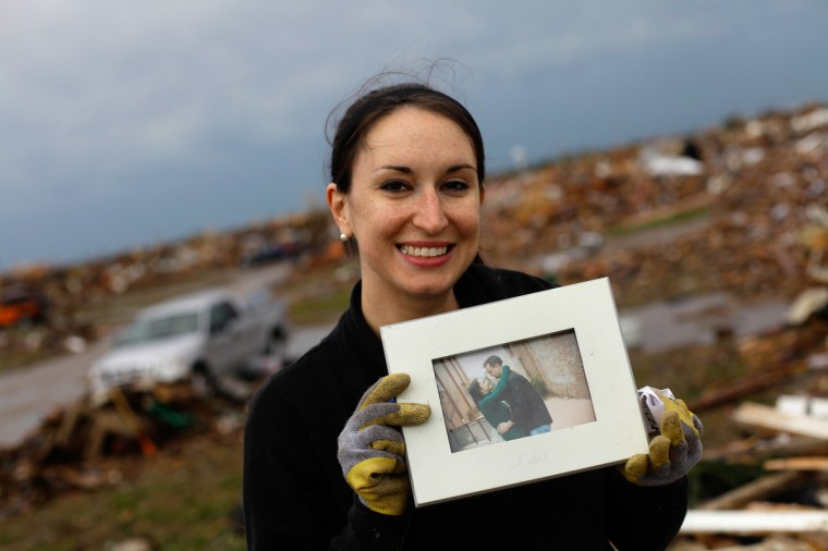 Kalissa Graham reacts after finding an engagement photo of her and her husband Roger Graham in the the rubble of her destroyed home on May 21, 2013 in Moore, Oklahoma. Families returned to a blasted moonscape that had been an American suburb Tuesday after a monstrous tornado tore through the outskirts of Oklahoma City, killing at least 24 people. Nine children were among the dead and entire neighborhoods vanished, with often the foundations being the only thing left of what used to be houses and cars tossed like toys and heaped in big piles. (Joshua Lott/Getty Images)