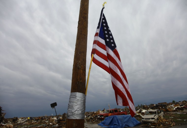 The American flag is tapped to a pole as it hangs in the foreground of destroyed houses and vehicles on May 21, 2013 in Moore, Oklahoma. Families returned to a blasted moonscape that had been an American suburb Tuesday after a monstrous tornado tore through the outskirts of Oklahoma City, killing at least 24 people. Nine children were among the dead and entire neighborhoods vanished, with often the foundations being the only thing left of what used to be houses and cars tossed like toys and heaped in big piles. (Joshua Lott/Getty Images)