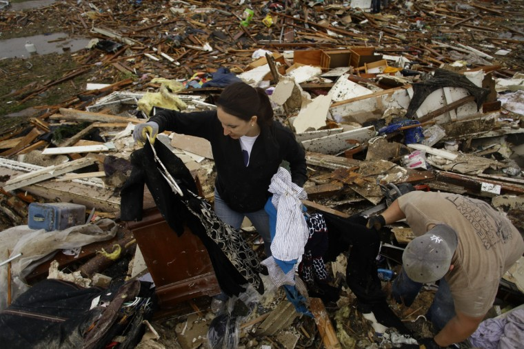 Kalissa Graham retrieves her belongings from her destroyed home with the help of her friend Derick Colwell on May 21, 2013 in Moore, Oklahoma. Families returned to a blasted moonscape that had been an American suburb Tuesday after a monstrous tornado tore through the outskirts of Oklahoma City, killing at least 24 people. Nine children were among the dead and entire neighborhoods vanished, with often the foundations being the only thing left of what used to be houses and cars tossed like toys and heaped in big piles. (Joshua Lott/Getty Images)