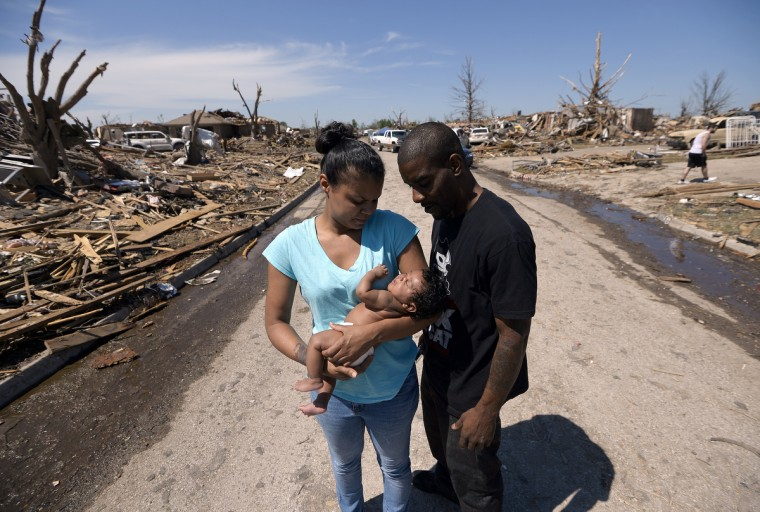 Tornado survivor Arlisha Hall holds her 2-month-old daughter Akai Hall as she along with her husband Wyatt Hall walk back to their home in Moore, Oklahoma. (Jewel Samad/Getty Images)