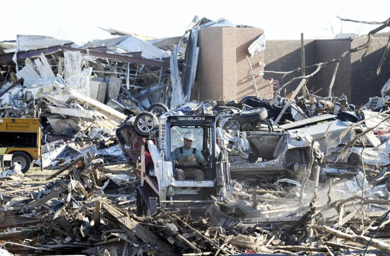 A man operates a bulldozer to clean debris from the front of tornado devastated Plaza Towers Elementary School in Moore, Oklahoma. Seven children died in the school during the tornado. (Jewel Samad/Getty Images)