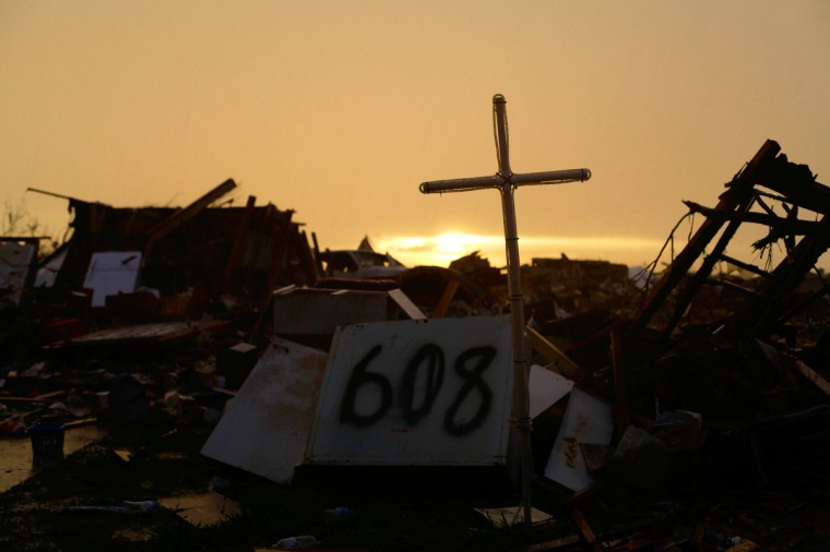 A cross stands over a destroyed home as the sun rises in Moore, Oklahoma. A powerful tornado classified as an EF4 passed through the town May 20, destroying homes, schools and businesses and killing 24 people including children. (Joshua Lott/Getty images)