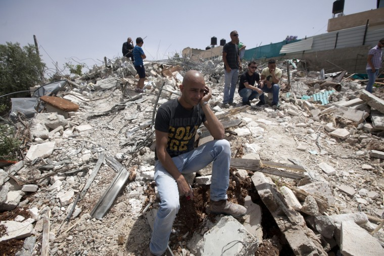 A man sits on the rubble of a Palestinian home after it was torn down by Israeli bulldozers in the Arab east Jerusalem neighborhood of Beit Hanina. Palestinian homes built without a construction permit are often demolished by order of the Jerusalem municipality. (Ahmad Gharabli/Getty Images)