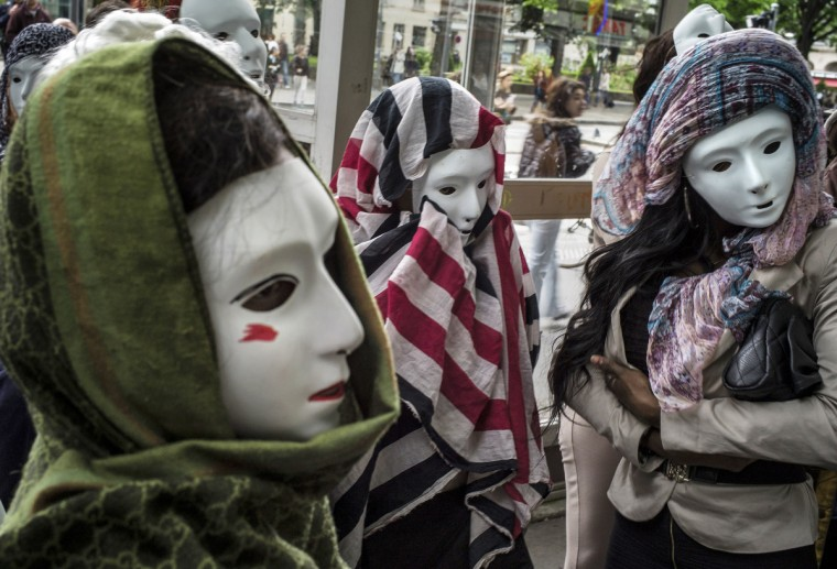 Prostitutes wearing masks demonstrate in Lyon, to denounce their working conditions and police repression. (Jeff Pachoud/Getty Images)