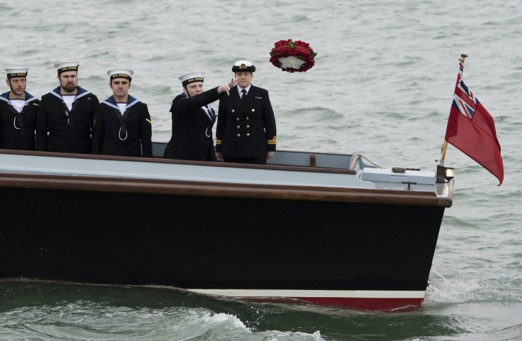Able Seaman 1st Class Luke Checkley (2nd R) and crew members of HMS Duncan, the latest Type 45 destroyer, throws a wreath from the deck of WWII seaplane tender during a ceremony at the wreck site of the 16th century Tudor warship Mary Rose commemorating those who died when she sank in 1545 in The Solent near Portsmouth The relics from the Mary Rose, the flagship of England's navy when it sank in 1545 as a heartbroken king Henry VIII watched from the shore, have finally been reunited with the famous wreck in a new museum offering a view of life in Tudor times. (Adrian Dennis/Getty Images)